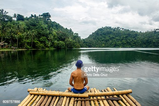 Topless man in the middle of the lake sitting on bamboo : Stock Photo