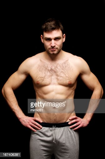 Topless man stood isolated on a black background : Stock Photo