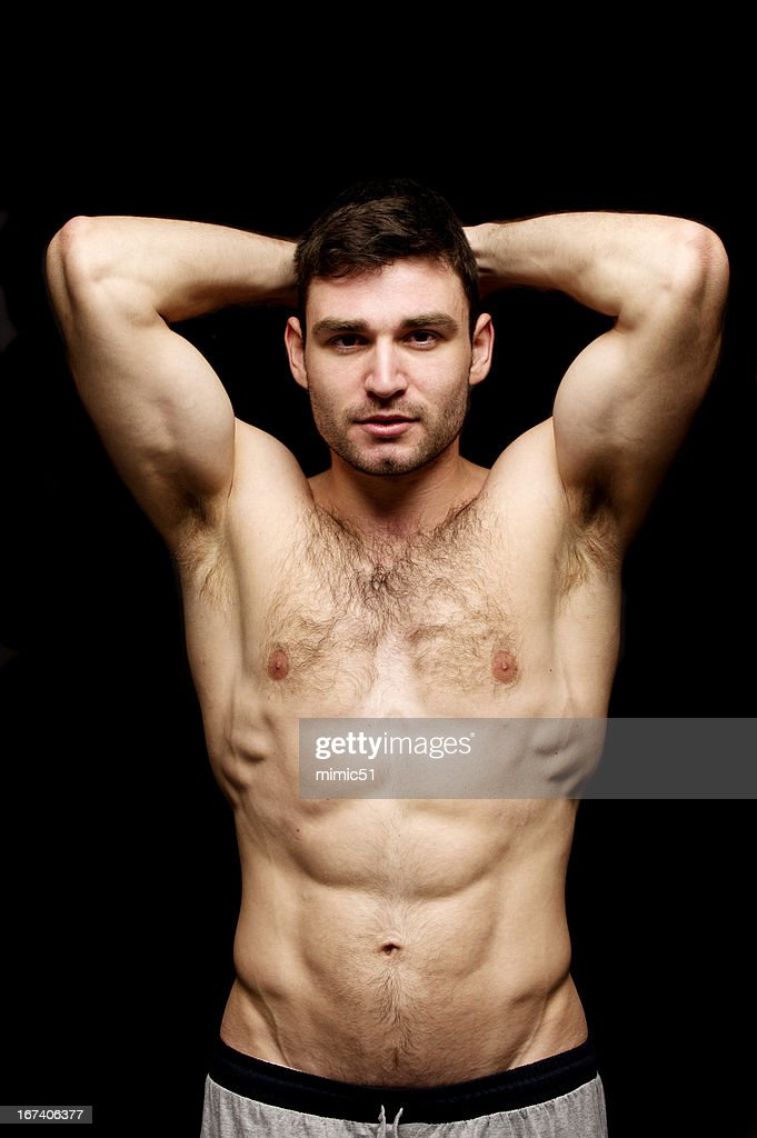 Topless man stood on a black background : Stock Photo