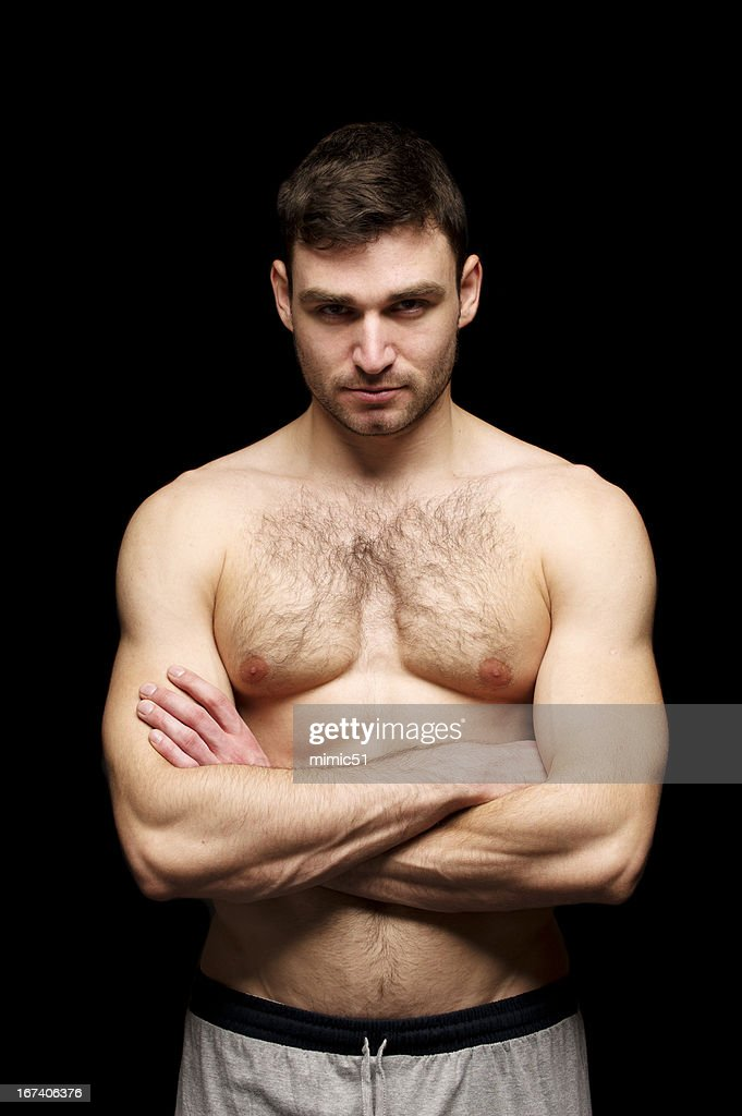Topless man stood with his arms folded : Stock Photo