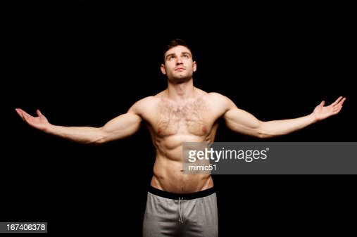Topless man stood with his arms outstretched : Stock Photo