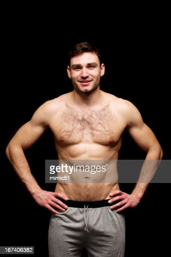 Topless man stood with his hands on hips : Stockfoto