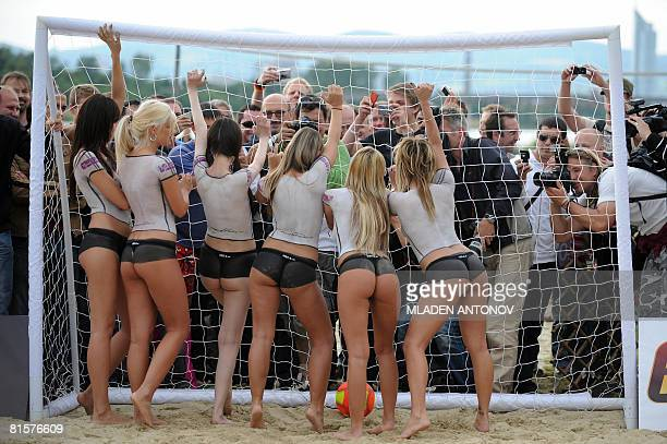 Topless porn actresses wearing bodypaint with German colours pose before a beach football game on a beach in Vienna on June 15 a day before the...