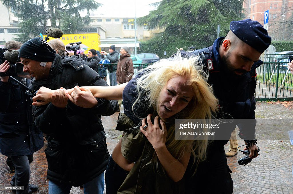 A topless protester is taken away by police officers at a polling station where former Italian Prime Minister Silvio Berlusconi was casting his vote on February 24, 2013 in Milan, Italy. Three half-naked protesters with 'Basta Berlusconi' ('Enough With Berlusconi') written on their backs rushed toward Berlusconi but failed to reach him.
