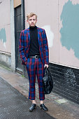 Topman suit specialist and fashion blogger Johnny Clark wearing a Topman suit and polo neck New Look shoes and a River Island bag on day 2 of London...