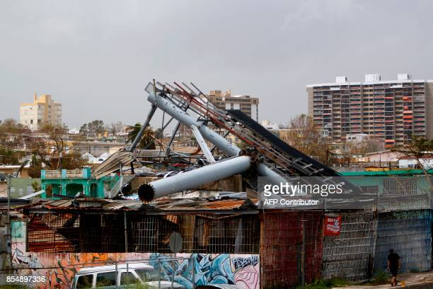 A toppled electronic billboard lies atop a house one week after the passage of Hurricane Maria in San Juan Puerto Rico on September 27 2017 The US...