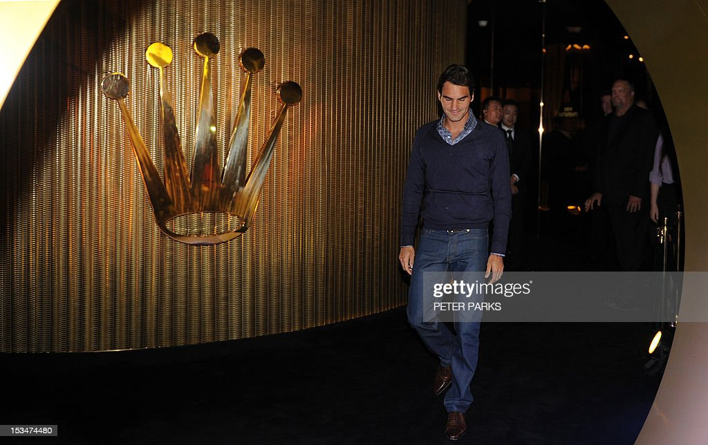 Top-ranked men's tennis player Roger Federer (R) of Switzerland arrives for the draw for the Shanghai Masters tennis tournament in Shanghai on October 6, 2012. Federer will have to shrug off a bizarre death threat as he returns to action at the Shanghai Masters from October 7 to combat Novak Djokovic's attempt on his world number one crown. AFP PHOTO / Peter PARKS