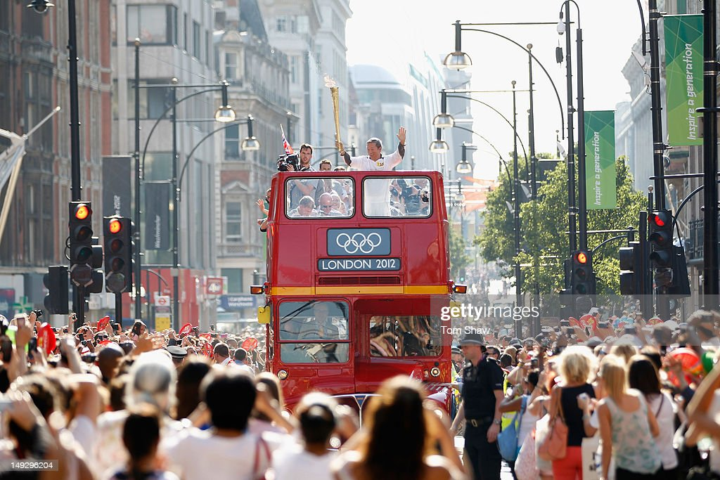 A torch bearer carrries the Olympic Torch on a London Bus through Central London on July 26, 2012 in London, England.