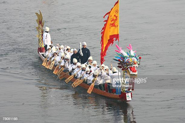 A torch bearer holds the torch in a dragonboat during the torch relay for the 6th Asian Winter Games on January 20 2007 in Jilin City of Jilin...