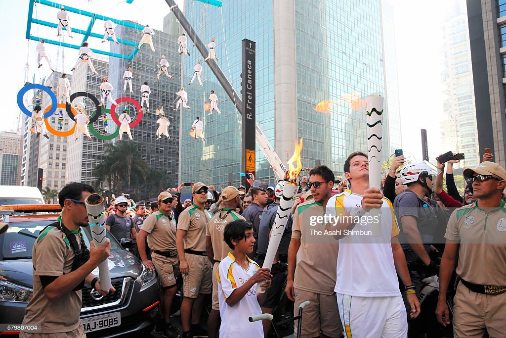 Torch bearers are seen as the Olympic torch relay arrive at Sao Paulo on July 24, 2016 in Sao Paulo, Brazil.