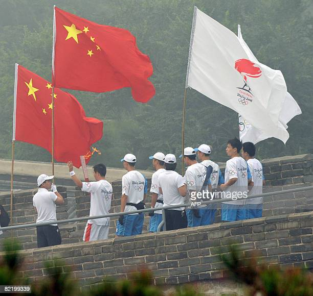 A torchbearer carries the Olympic flame in the Olympic torch relay along a section of the Great Wall in Badaling outside Beijing on August 07 2008...