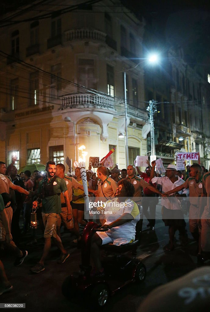 A torchbearer carries the Olympic flame on May 31, 2016 in Recife, Brazil. The Olympic flame will pass through 329 cities from all states from the north to the south of Brazil, before arriving in Rio de Janeiro on August 5, for the lighting of the cauldron for the Rio 2016 Olympic Games. The games will be held amidst an economic and political crisis in the country.