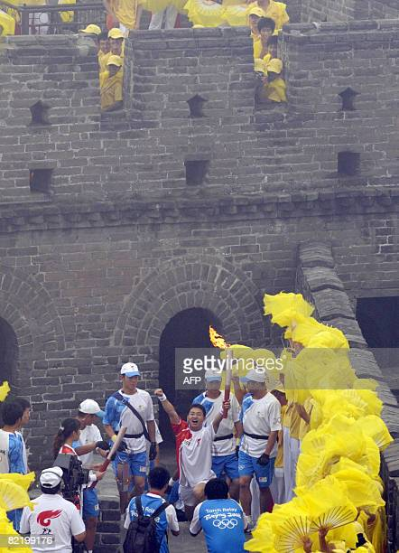 A torchbearer gestures as he carries the Olympic flame in the Olympic torch relay along a section of the Great Wall in Badaling outside Beijing on...