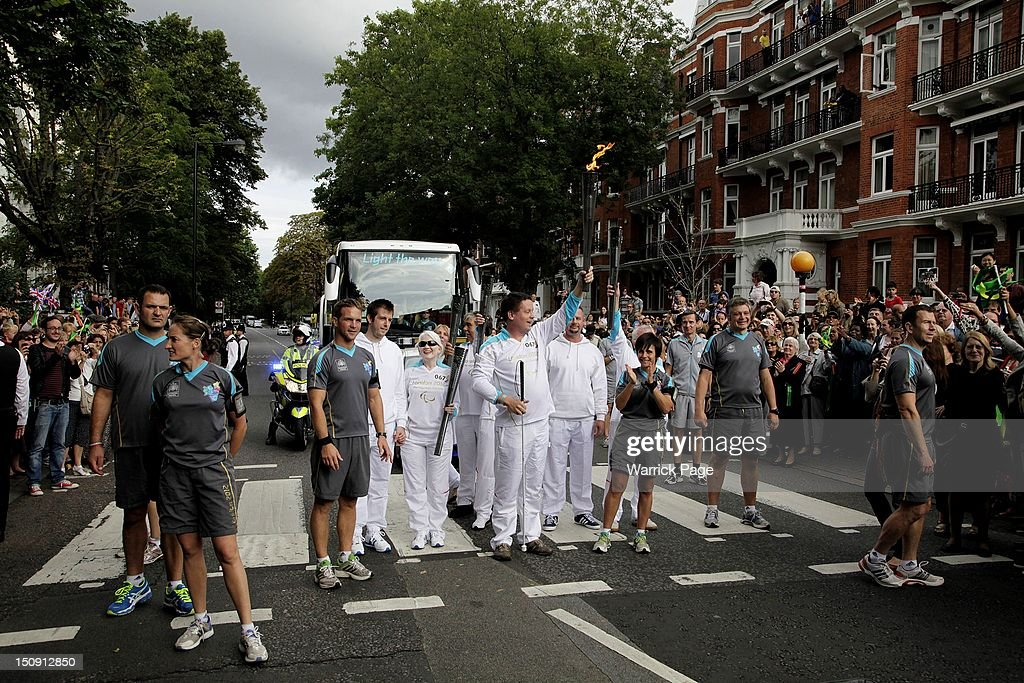 Torchbearer Graham Helm raises the Paralympic torch at the Abbey Road pedestrian crossing, made famous by the Beatles 'Abbey Road' album cover, ahead of the start of the London 2012 Paralympic Games on August 29, 2012, in London, England.