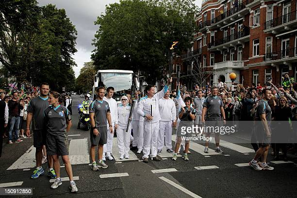 Torchbearer Graham Helm raises the Paralympic torch at the Abbey Road pedestrian crossing made famous by the Beatles 'Abbey Road' album cover ahead...