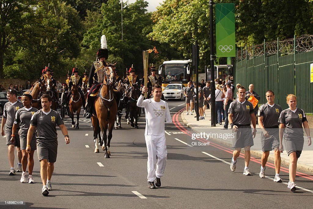 Torchbearer Jaco van Gass (C), a soldier with the First Battalion, The Parachute Regiment, who was severely wounded in Afghanistan, is followed by the Kings Troop Royal Horse Artillery as he carries the Olympic torch past Woolwich Barracks on July 21, 2012 in London, England. The 64th day of the Olympic torch relay will see torchbearers carry the flame through the capital for the first full day in London ahead of the 2012 Olympic Games.