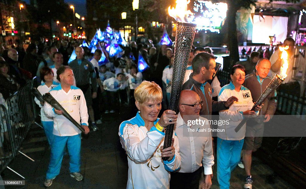 Torchbearer Janet Gray (C) carries the 2012 Paralympic torch on August 25, 2012 in Belfast, Northern Ireland.