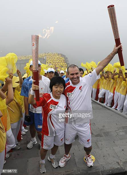 Torchbearers Liu Fang a student and Colin Giles of Nokia take part in the Olympic torch relay along a section of the Great Wall in Badaling outside...