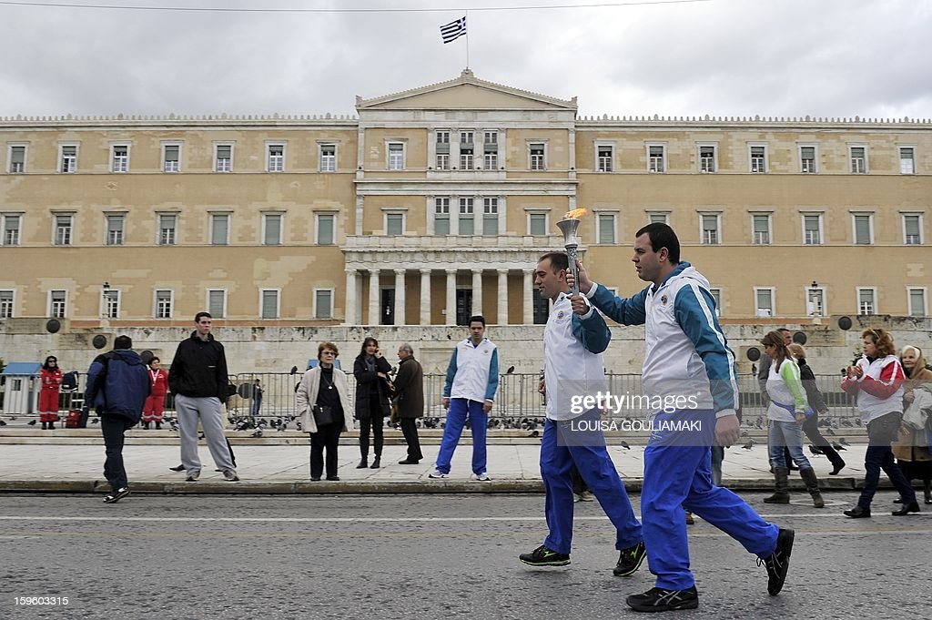 Torchbearers run past the Greek parliament during a torch relay of the 'Flame of Hope' for the 2013 Pyeong Chang World Winter Games at the Zappion megaron in Athens on January 17, 2012. AFP PHOTO/ Louisa Gouliamaki