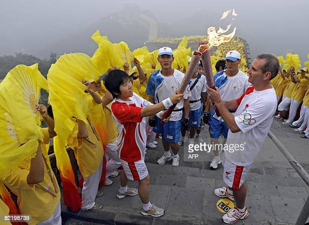 Torchbearers Wang Ning and Colin Giles exchange the flame as they take part in the Olympic torch relay along a section of the Great Wall in Badaling...
