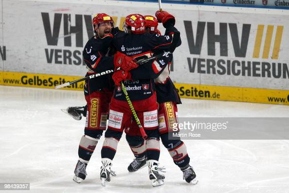 Tore Vikingstad Andre Reiss and Sascha Goc of Hannover celebrate after winning the third DEL play off semi final match between Hannover Scorpions and...