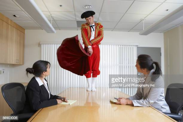 A toreador performing in a business office