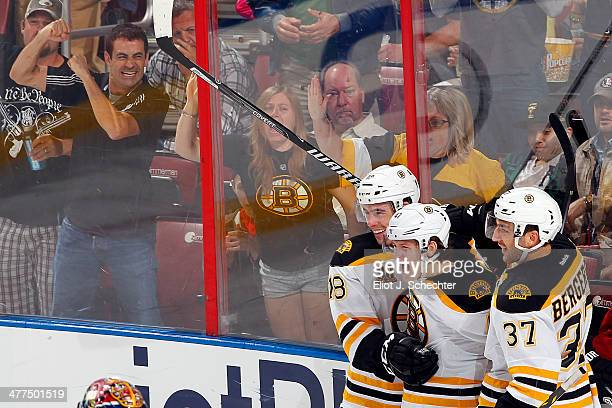 Torey Krug of the Boston Bruins celebrates his goal with teammates Reilly Smith and Patrice Bergeron against the Florida Panthers at the BBT Center...