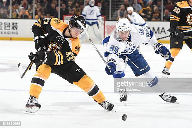 Torey Krug of the Boston Bruins fights for the puck against Nikita Kucherov of the Tampa Bay Lightning at the TD Garden on November 27 2016 in Boston...