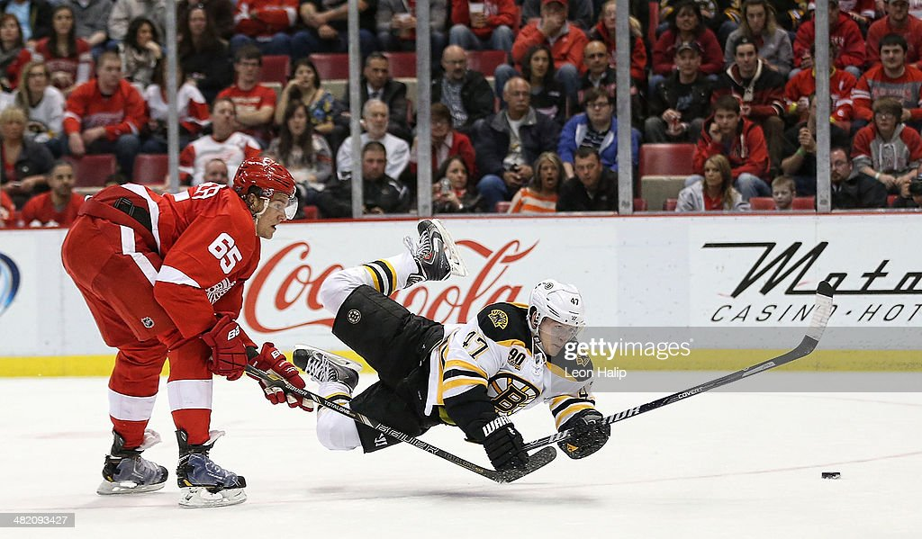 Torey Krug #47 of the Boston Bruins gets the shot off on goalie Jimmy Howard #35 of the Detroit Red Wings as defenseman Danny DeKeyser #65 defends during the second period of the game at Joe Louis Arena on April 2, 2014 in Detroit, Michigan.