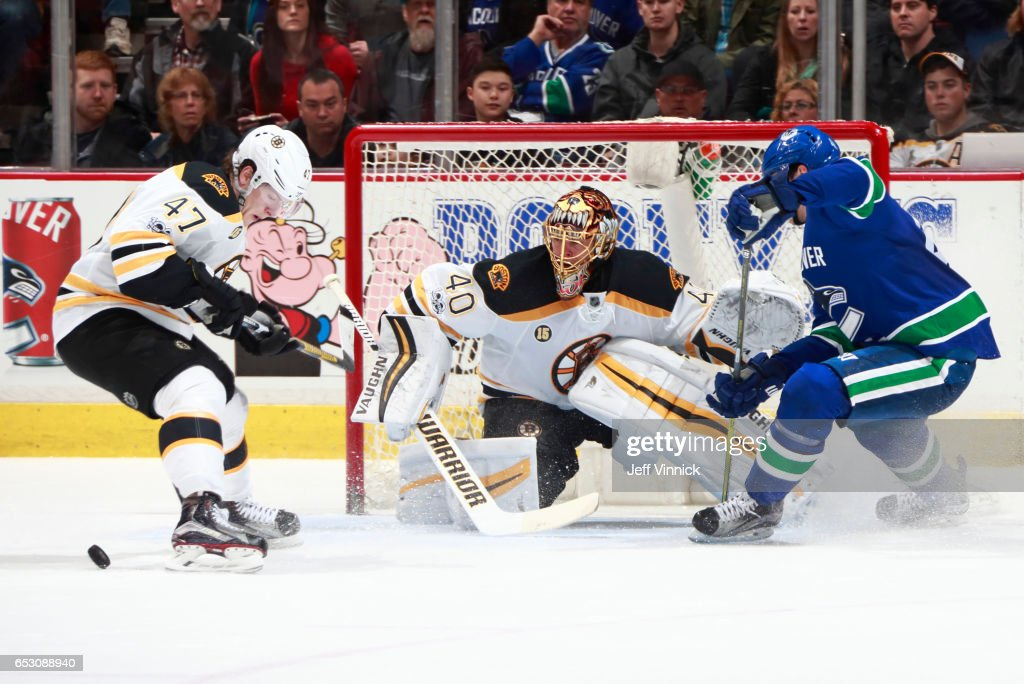 Torey Krug #47 of the Boston Bruins looks on as Tuukka Rask #40 of the Boston Bruins makes a save off the shot of Sven Baertschi #47 of the Vancouver Canucks during their NHL game at Rogers Arena March 13, 2017 in Vancouver, British Columbia, Canada. Boston won 6-3.