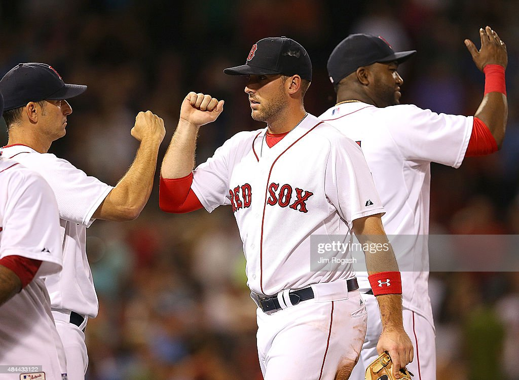 Torey Lovullo #17 of the Boston Red Sox and Travis Shaw #47, who had a four-hit game, celebrate a 9-1 win over the Cleveland Indians at Fenway Park on August 18, 2015 in Boston, Massachusetts.