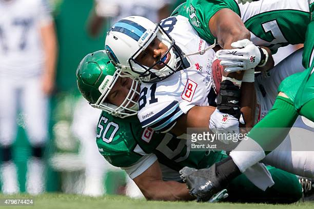 Tori Gurley of the Toronto Argonauts is tackled by Jake Doughty of the Saskatchewan Roughriders in the game between the Toronto Argonauts and...
