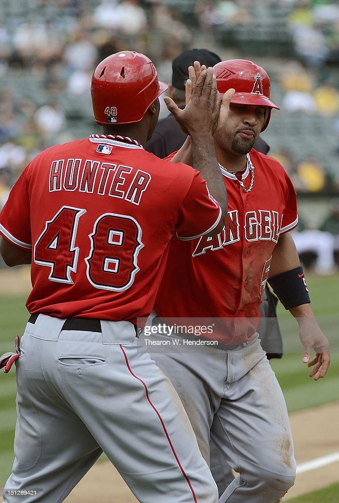 <a gi-track='captionPersonalityLinkClicked' href=/galleries/search?phrase=Torii+Hunter&family=editorial&specificpeople=183408 ng-click='$event.stopPropagation()'>Torii Hunter</a> #48 and <a gi-track='captionPersonalityLinkClicked' href=/galleries/search?phrase=Albert+Pujols&family=editorial&specificpeople=171151 ng-click='$event.stopPropagation()'>Albert Pujols</a> #5 of the Los Angeles Angels of Anaheim celebrates after they both scored on a two run single from Howie Kendrick #47 in the third inning against the Oakland Athletics at O.co Coliseum on September 5, 2012 in Oakland, California.