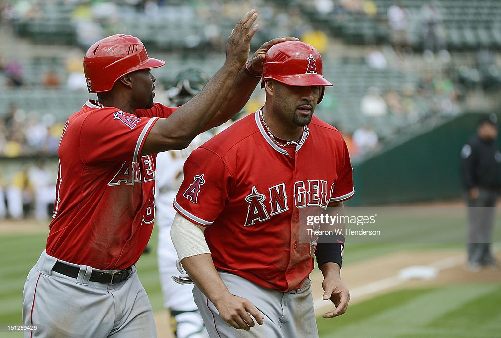 <a gi-track='captionPersonalityLinkClicked' href=/galleries/search?phrase=Torii+Hunter&family=editorial&specificpeople=183408 ng-click='$event.stopPropagation()'>Torii Hunter</a> #48 and <a gi-track='captionPersonalityLinkClicked' href=/galleries/search?phrase=Albert+Pujols&family=editorial&specificpeople=171151 ng-click='$event.stopPropagation()'>Albert Pujols</a> #5 of the Los Angeles Angels of Anaheim celebrate after they both scored on a two run single from Howie Kendrick #47 in the third inning against the Oakland Athletics at O.co Coliseum on September 5, 2012 in Oakland, California.