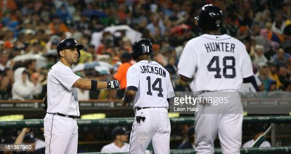 Torii Hunter and Austin Jackson of the Detroit Tigers celebrate with teammate Omar Infante after scoring on a single to centerfield by Andy Dirks...