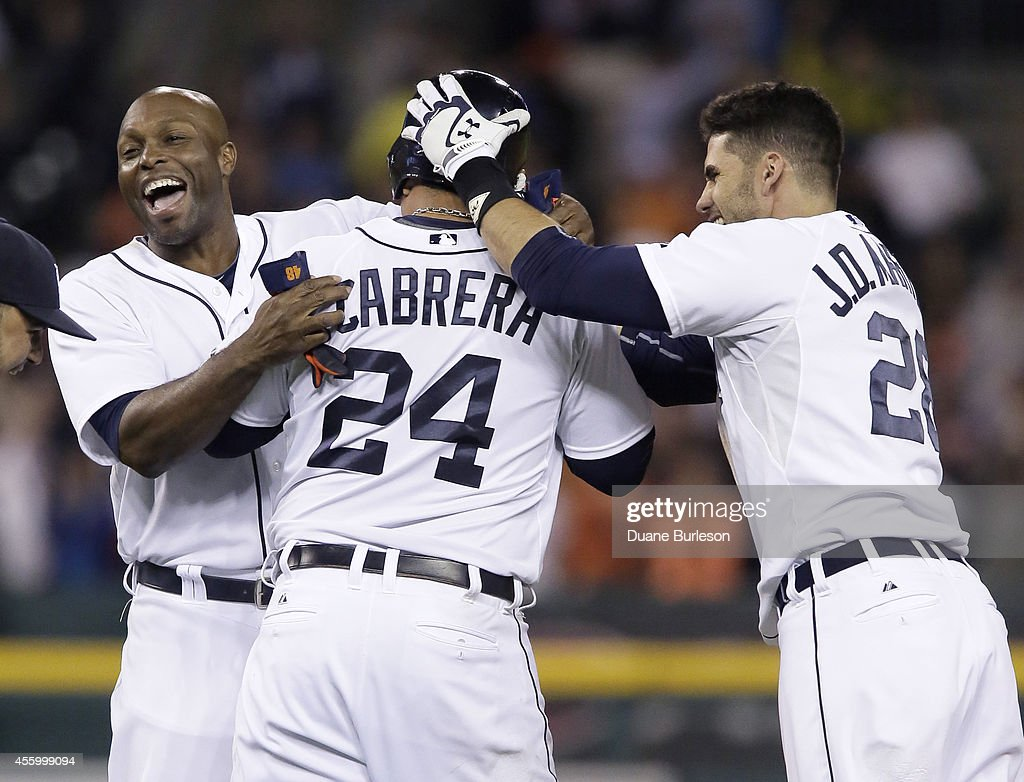 Torii Hunter #48 of the Detroit Tigers and J.D. Martinez #28 surround Miguel Cabrera #24 after he hit a RBI-single in the ninth inning to defeat the Chicago White Sox 4-3 at Comerica Park on September 23, 2014, in Detroit, Michigan.