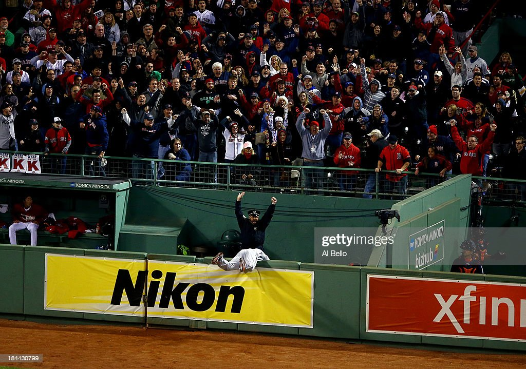 <a gi-track='captionPersonalityLinkClicked' href=/galleries/search?phrase=Torii+Hunter&family=editorial&specificpeople=183408 ng-click='$event.stopPropagation()'>Torii Hunter</a> #48 of the Detroit Tigers falls over the bullpen fence after trying to catch a grand slam hit by David Ortiz #34 of the Boston Red Sox as Boston Police Officer Steve Horgan celebrates in the eighth inning as Boston police officer Steve Horgan cheers in Game Two of the American League Championship Series at Fenway Park on October 13, 2013 in Boston, Massachusetts.