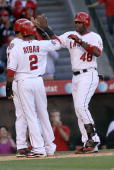 Torii Hunter of the Los Angeles Angels of Anaheim is greeted at home plate by Erick Aybar and Bobby Abreu as they all score on Hunter's three run...