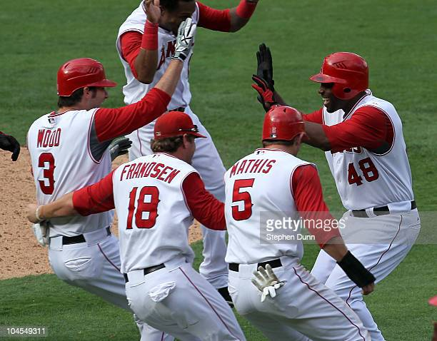 Torii Hunter of the Los Angeles Angels of Anaheim is mobbed by Brandon Wood Kevin Frandsen and Jeff Mathis after Hunter's walk off single in the 11th...