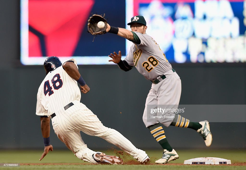 Torii Hunter #48 of the Minnesota Twins slides back to second base as Eric Sogard #28 of the Oakland Athletics fields the throw from pitcher Scott Kazmir #26 during the third inning of the game on May 6, 2015 at Target Field in Minneapolis, Minnesota. The Twins defeated Athletics 13-0.