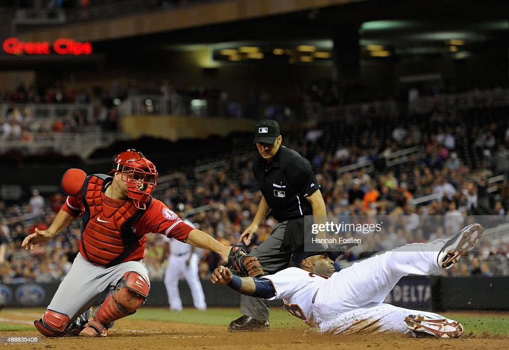 Torii Hunter of the Minnesota Twins slides safely into home plate to score a run as Chris Iannetta of the Los Angeles Angels of Anaheim applies the...