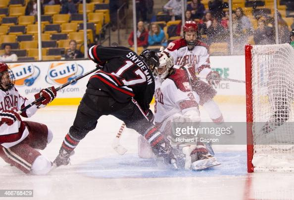 Torin Snydeman of the Northeastern University Huskies shoots the puck into the net behind Raphael Girard of the Harvard Crimson during NCAA hockey...