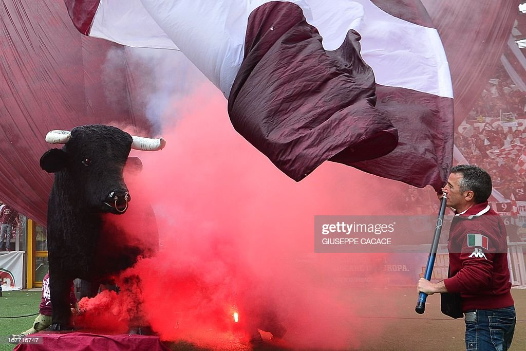 A Torino supporter waves his team's colours next to a statue of a bull before the Italian Serie A football match between Torino and Juventus on April 28, 2013 at the Olympic Stadium in Turin.