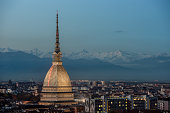 View of Turin at twilight with the illuminated Mole Antonelliana and the snow capped peaks of the Alps on the background.