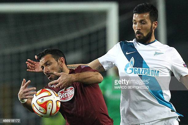 Torino's forward Fabio Quagliarella fights for the ball with Zenit's Argentinian defender Ezequiel Garay during the UEFA Europa League round of 16...