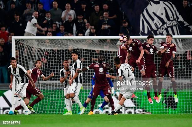 Torino's Italian forward Andrea Belotti stops a kick of Juventus' Argentinian forward Paulo Dybala during the Italian Serie A football match Juventus...