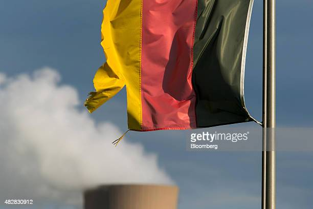 A torn German national flag flies as a cooling tower emits vapor at Grohnde nuclear power plant operated by EON SE in Grohnde Germany on Thursday...