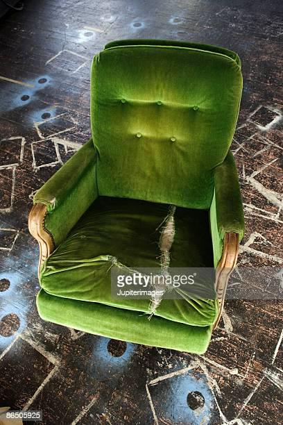 Torn green velvet chair