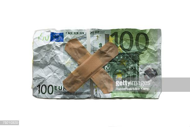 Torn one hundred euro banknote with bandages