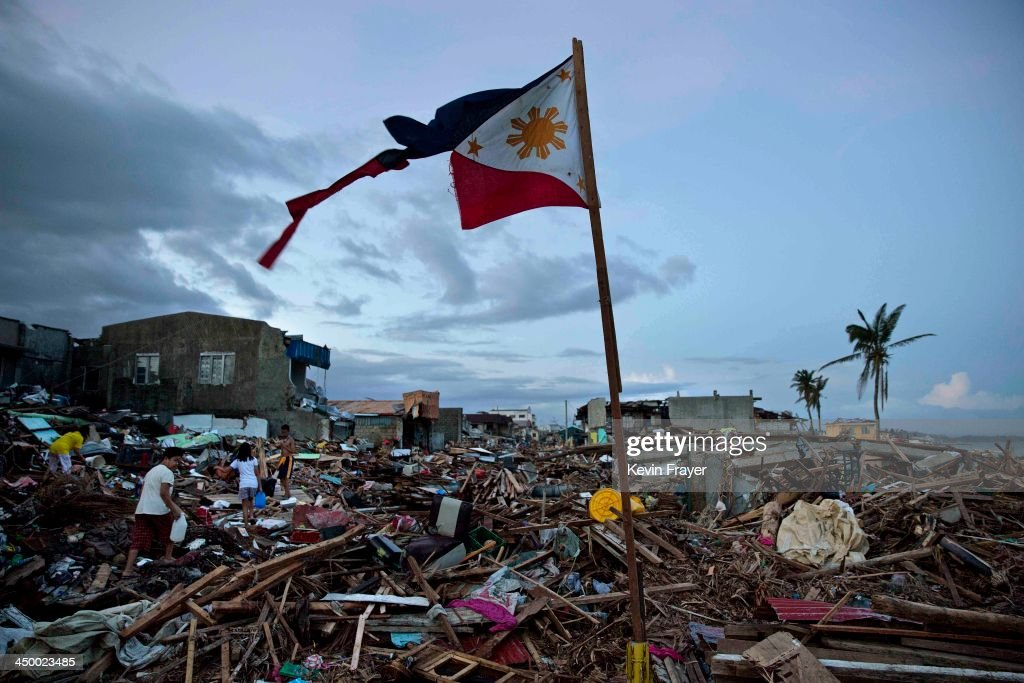 A torn Philippines flag stands in the rubble in the aftermath of Typhoon Haiyan November 16, 2013 in Tacloban, Philippines. Typhoon Haiyan has been described as one of the most powerful typhoons ever to hit land, leaving thousands dead and hundreds of thousands homeless. Countries all over the world have pledged relief aid to help support those affected by the typhoon, however damage to the airport and roads have made moving the aid into the most affected areas very difficult. With dead bodies left out in the open air and very limited food, water and shelter, health concerns are growing.